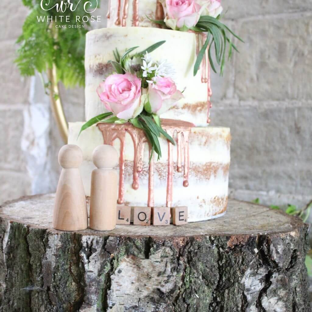 Three Tier Semi-Naked Wedding Cake with Fresh Flowers and Rose Gold Drips by White Rose Cake Design Bespoke Wedding Cakes in Huddersfield Holmfirth West Yorkshire