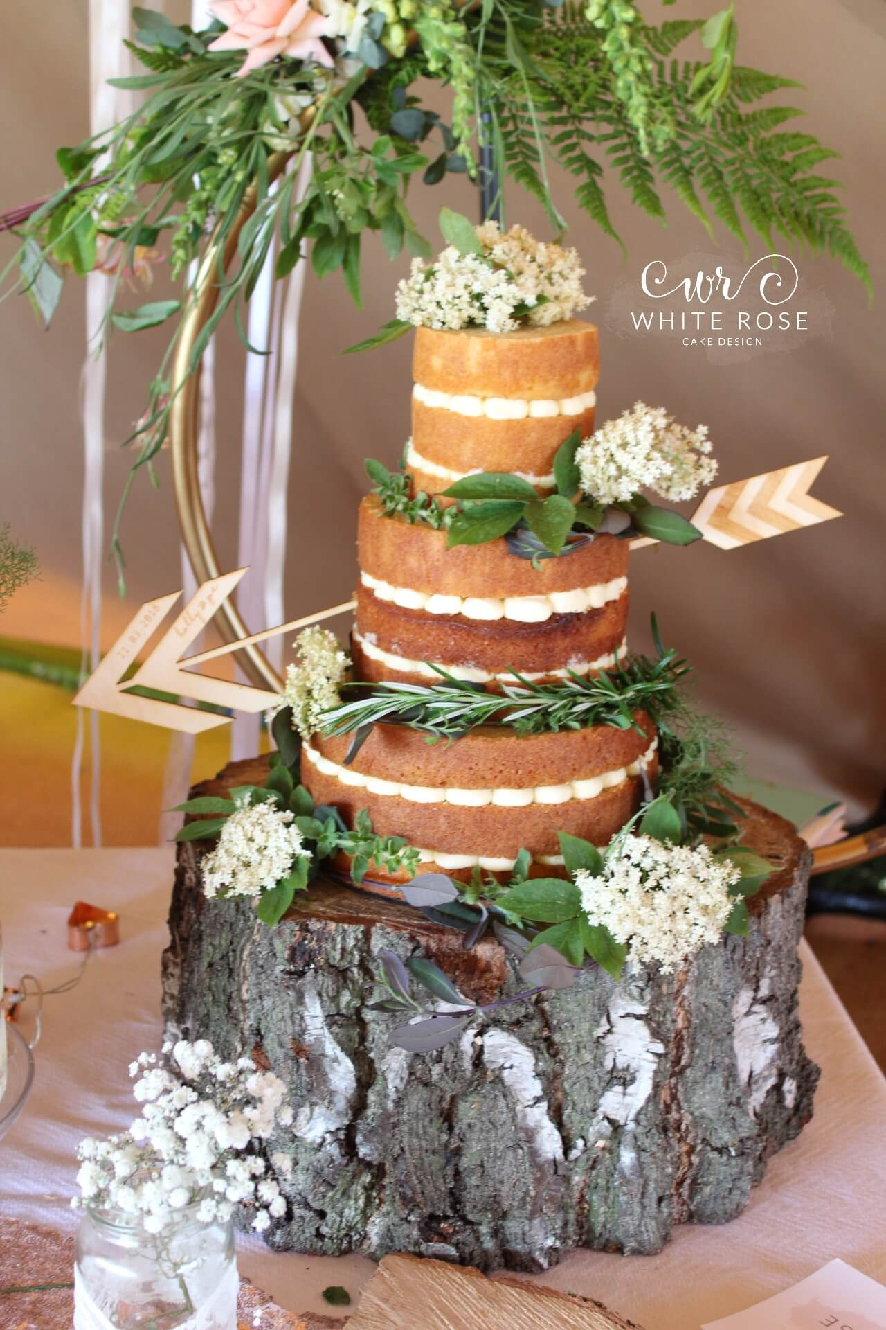 Rustic Three Tier Wedding Cake With Arrow And Elder Flowers On Log By White Rose