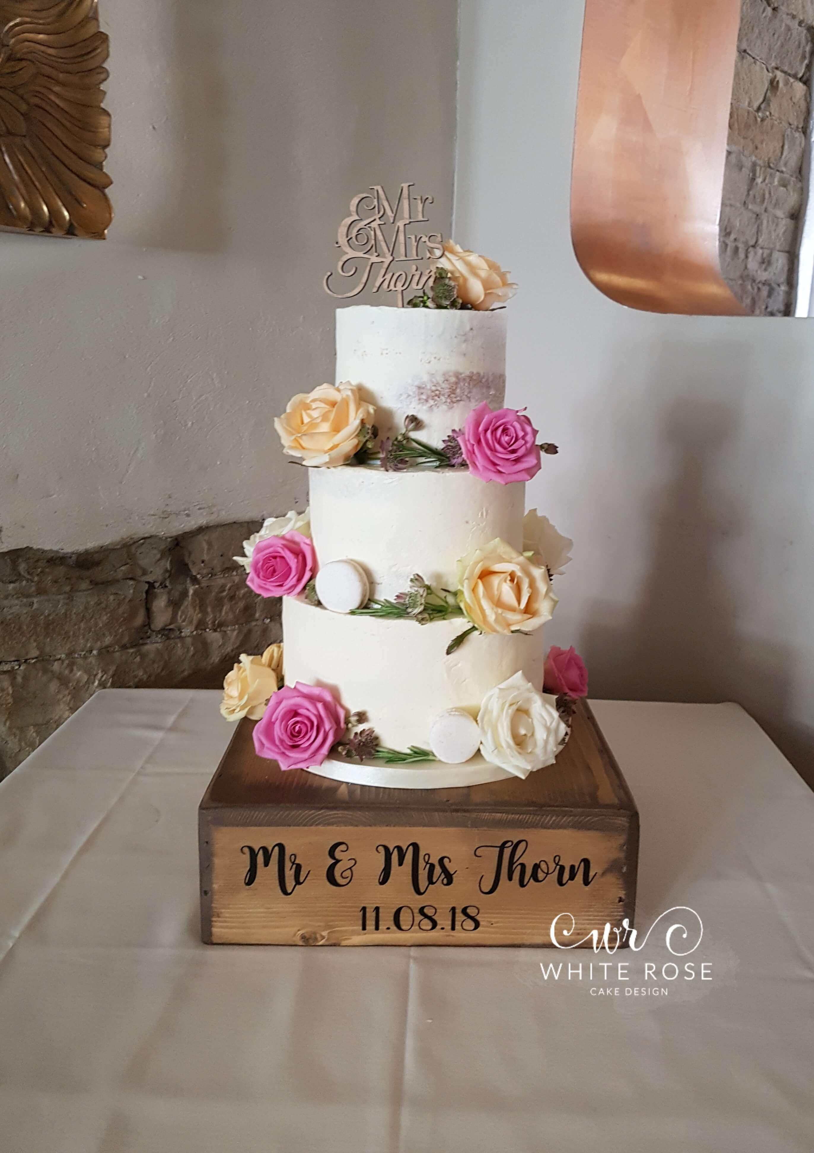 semi-Naked Wedding Cake with Fresh Roses and Macarons by White Rose Cake Design Bespoke Cake Makers in West Yorkshire