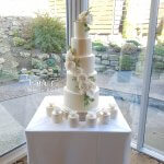 Elegant White 5 tier wedding cake with floral cascade by White Rose Cake Design luxury cake maker Huddersfield