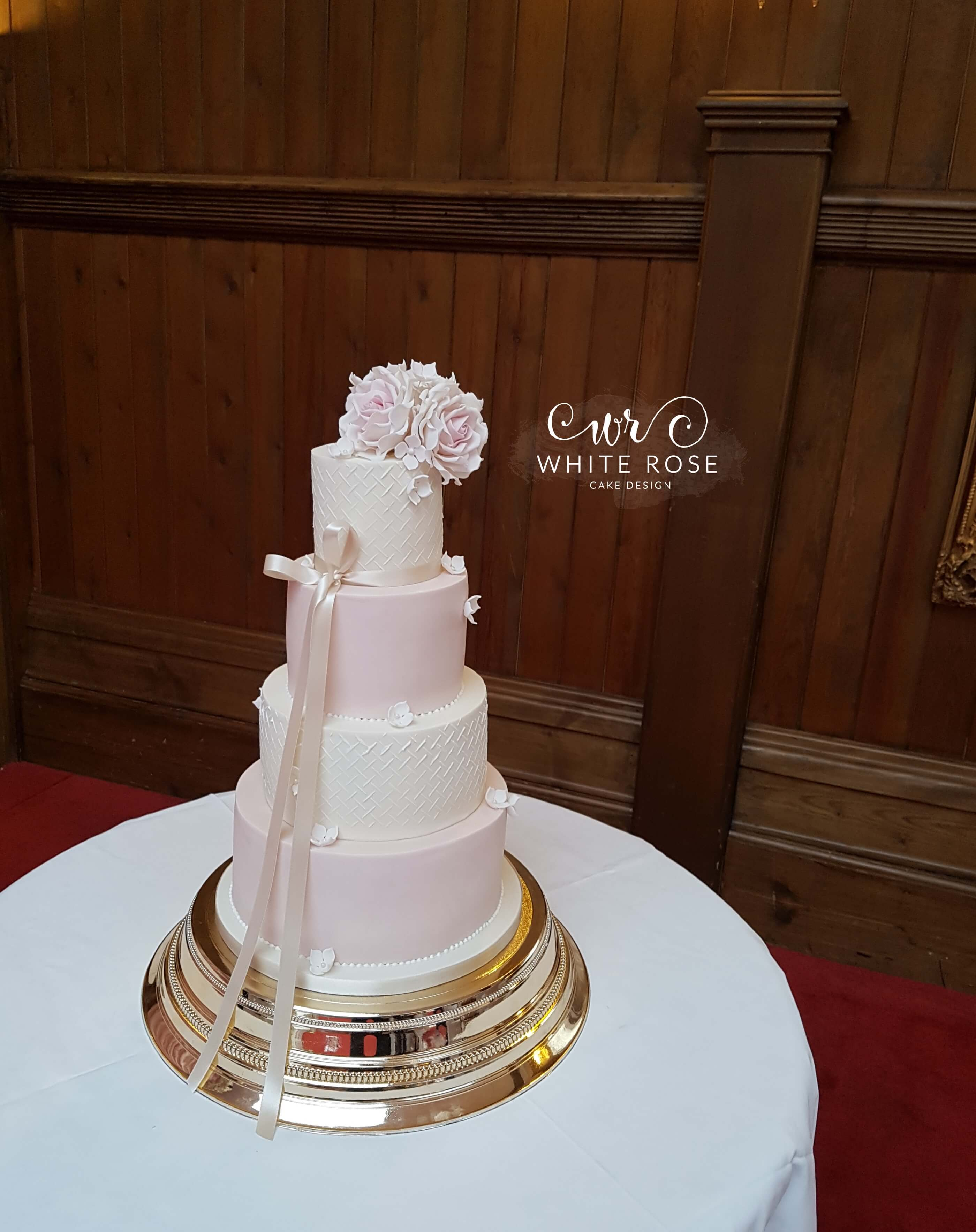 Four Tier Pink and White Wedding Cake with Gold Stand and Sugar Roses at Crossley House by White Rose Cake Design Bespoke Cake Makers in Holmfirth Halifax Huddersfield West Yorkshire