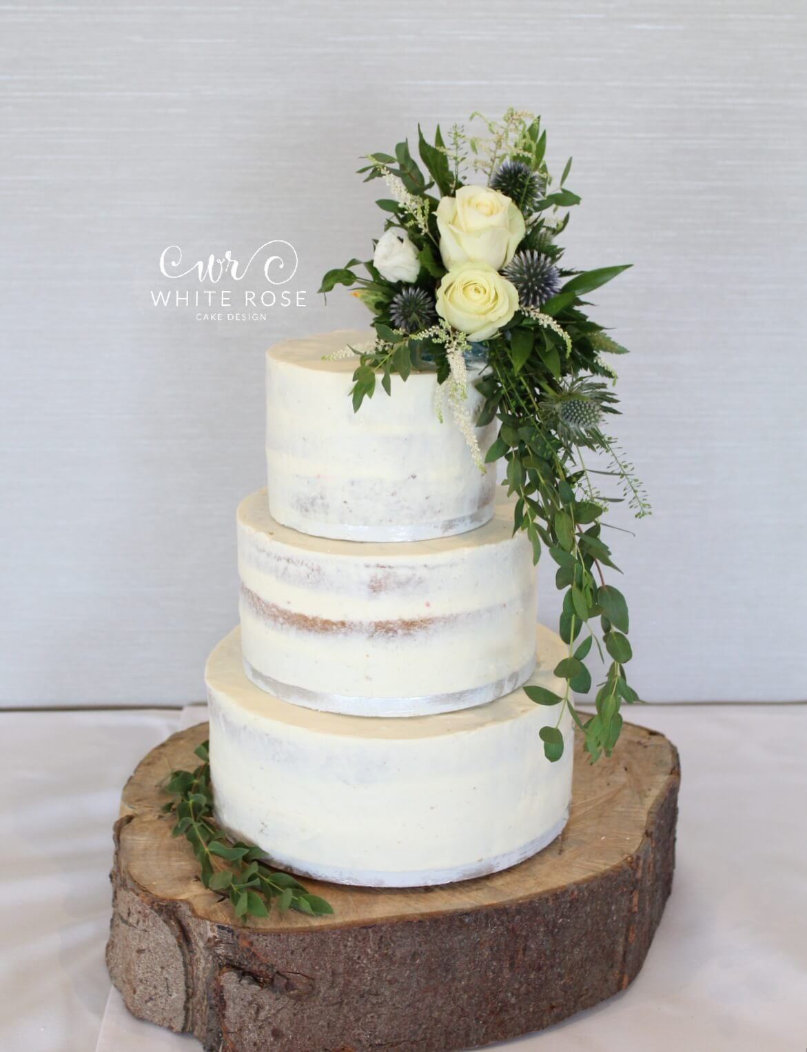 Rustic Semi-Naked Wedding Cake with Fresh Flowers at The Fleece Inn on rustic log stand by White Rose Cake Design Cake Maker in Halifax Huddersfield Holmfirth West Yorkshire