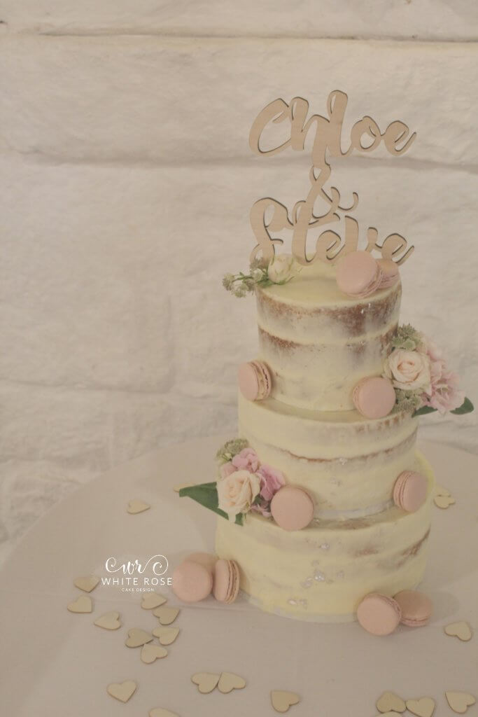 Semi-Naked Wedding Cake with Fresh Flowers and Pink Macarons at East Riddlesden Hall by White Rose Cake Design in Huddersfield Honley Holmfirth Bradford Yorkshire