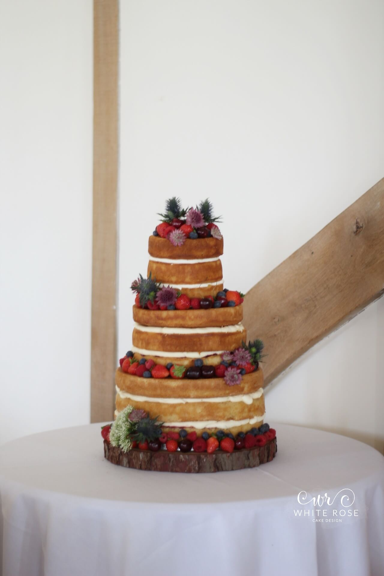 Whimsical Naked Wedding Cake with Fresh Berries and Flowers at Sandburn Hall by White Rose Cake Design Bespoke Cake Makers in West Yorkshire (1)