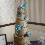 Woodland Tree Stump Wedding Cake with Blue Roses and Flower and Birds by White Rose Cake Design Rustic Wedding Cakes West Yorkshire